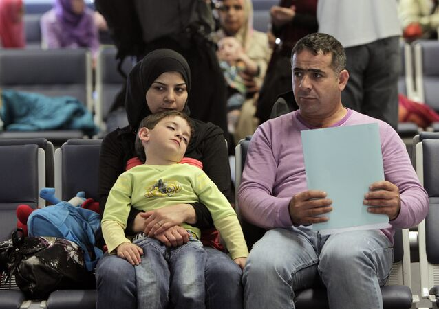 Syrian refugees wait to board a flight to Germany for temporary relocation, at Rafik Hariri International Airport in Beirut, Lebanon, Wednesday, Sept. 11, 2013.