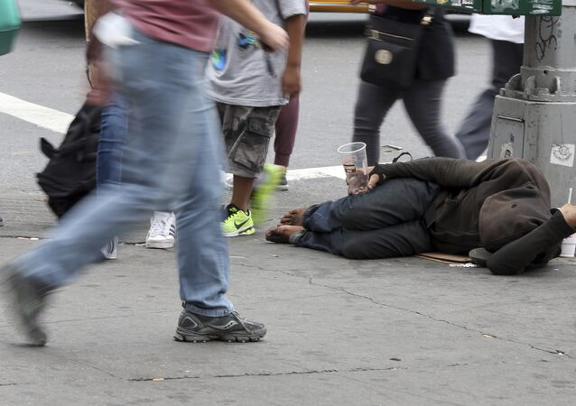 People walk past a homeless man asking for money on 14th Street, Friday, Sept. 4, 2015, in New York