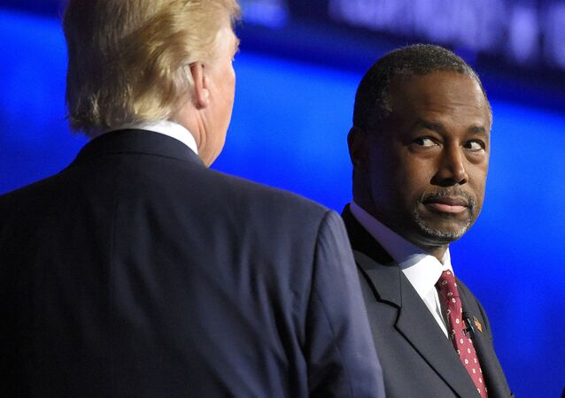 Ben Carson watches as Donald Trump takes the stage during the CNBC Republican presidential debate at the University of Colorado.