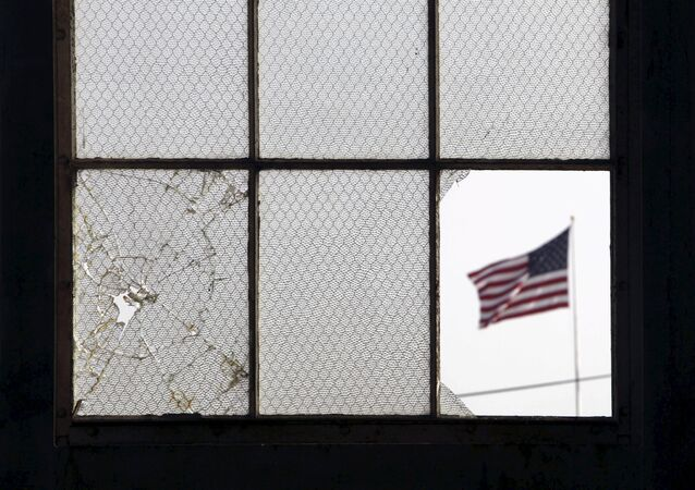 In this 2009 file photo, reviewed by the U.S. military, an American flag fluttering in the wind is pictured through a broken window from inside an airplane hangar used for media activities at Camp Justice, the site of the U.S. war crimes tribunal compound, at Guantanamo Bay U.S. Naval Base, Cuba, July 16, 2009