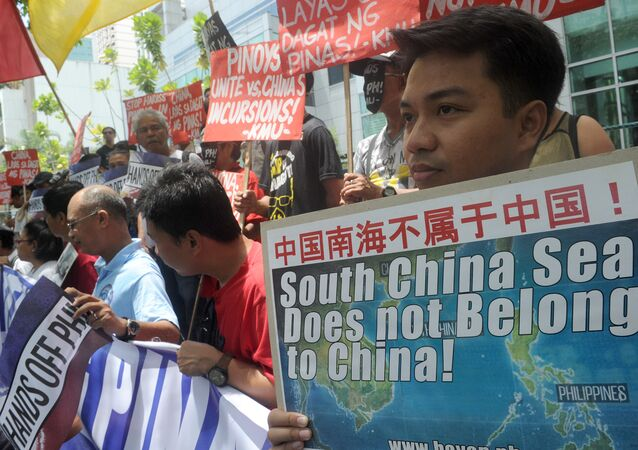 Protesters brandish placards at a rally in front of the Chinese Consulate in Manila's financial district on July 7, 2015, denouncing China's claim to most of the South China Sea including areas claimed by the Philippines