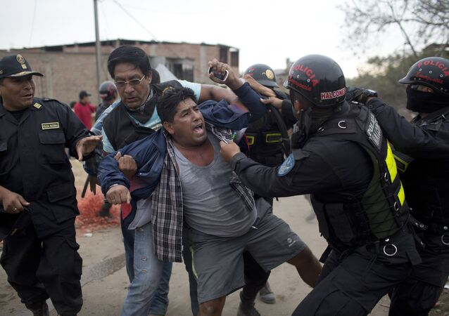 Riot police detain a man during a land eviction in Lima Peru,Tuesday, May 19, 2015