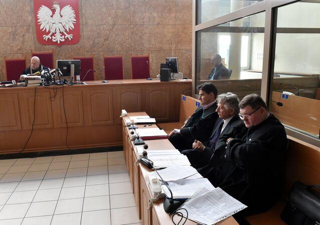 French-Polish film director Roman Polanski (C) sits between his lawyers Jerzy Stachowicz (L) and Jan Olszewski (R) at the District Court in Krakow, Poland, on September 22, 2015