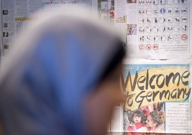 A woman waits in front of a wall newspaper in the initial reception center for asylum seekers in Halle/Saale, Germany, Friday, Oct. 16, 2015.