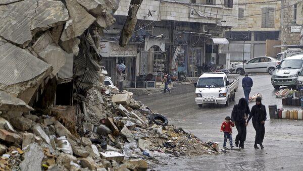Civilians walk in the rain past a damaged building in the rebel-controlled area of Maaret al-Numan town in Idlib province, Syria October 28, 2015 - Sputnik International