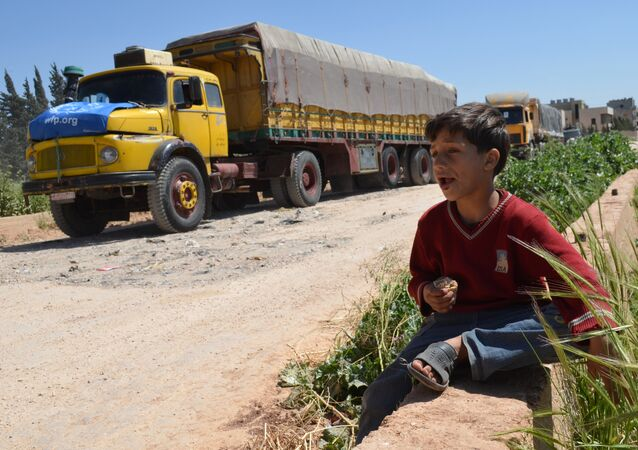 A Syrian child eats as he sits near a convoy of trucks from the World Food Programme and UNICEF carrying international aid as they drive in the countryside of the Homs district en route to the rebel held area of Al-Rastan north of the central Syrian city of Homs, on April 21, 2015.