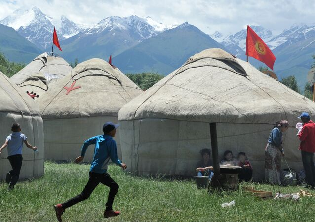 Boys run in front of yurtas (nomad's tent) during the 5th International Festival of Kyrgyz National Applied Arts in the village of At-Bashi, 400 km from Bishkek, on June 28, 2015