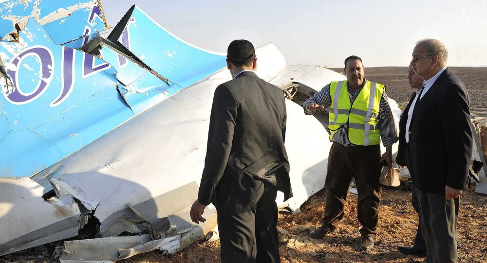In this image released by the Prime Minister's office, Sherif Ismail, right, looks at the remains of a crashed passenger jet in Hassana Egypt, Friday, Oct. 31, 2015
