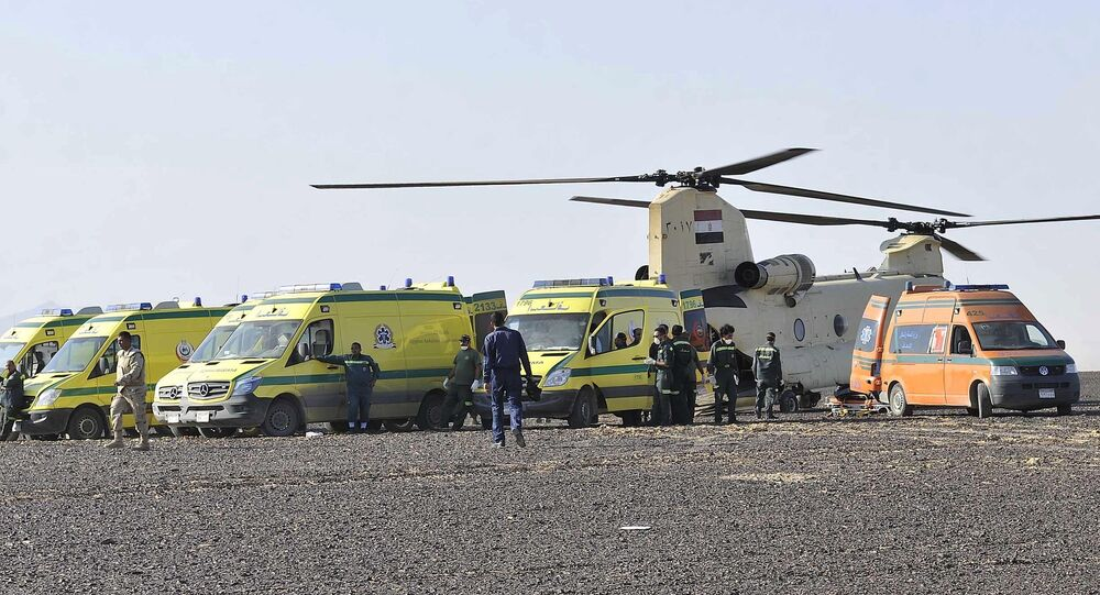 In this photo released by the Prime Minister's office, ambulances and a military helicopter stand by to transport bodies after a plane crashed in Hassana, Egypt on Saturday, Oct. 31, 2015.