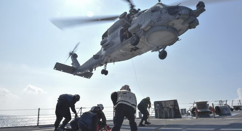 U.S. Navy Sailors participate in a medical training exercise on the deck of the Arleigh Burke-class guided missile destroyer USS Lassen (DDG 82) with an MH-60R Seahawk helicopter, in the South China Sea, October 28, 2015