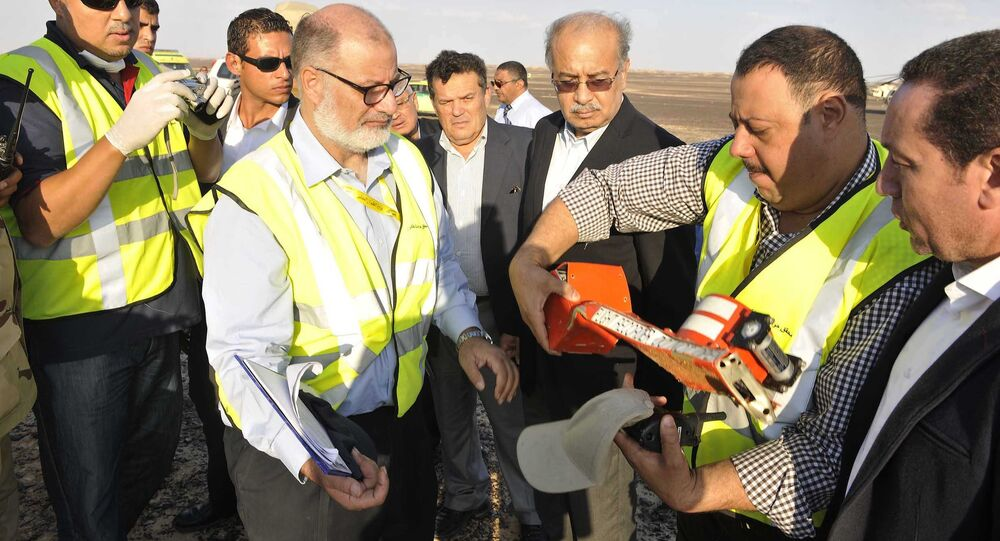 In this photo released by the Prime Minister's office, Sherif Ismail, third right, looks at the flight data recorder inspected by officials at the site where a passenger plane crashed in Hassana, Egypt on Saturday, Oct. 31, 2015