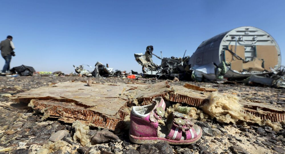 A child's shoe is seen in front of debris from a Russian airliner which crashed at the Hassana area in Arish city, north Egypt, November 1, 2015