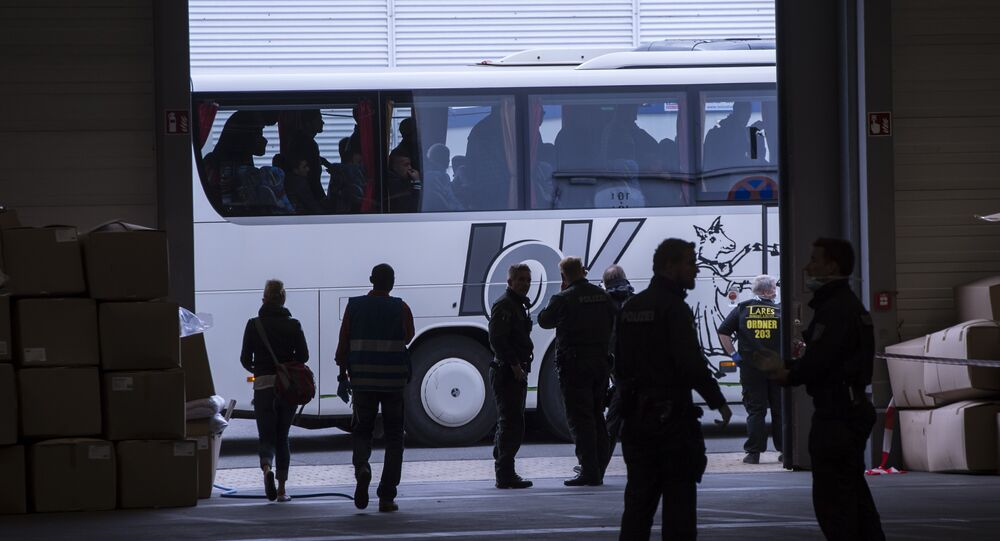 Refugees wait outside in a bus during their arrival in the accommodation, the exhibition halls of the Trade Fair Messe Erfurt, in Erfurt, central Germany, Tuesday, Sept. 8, 2015