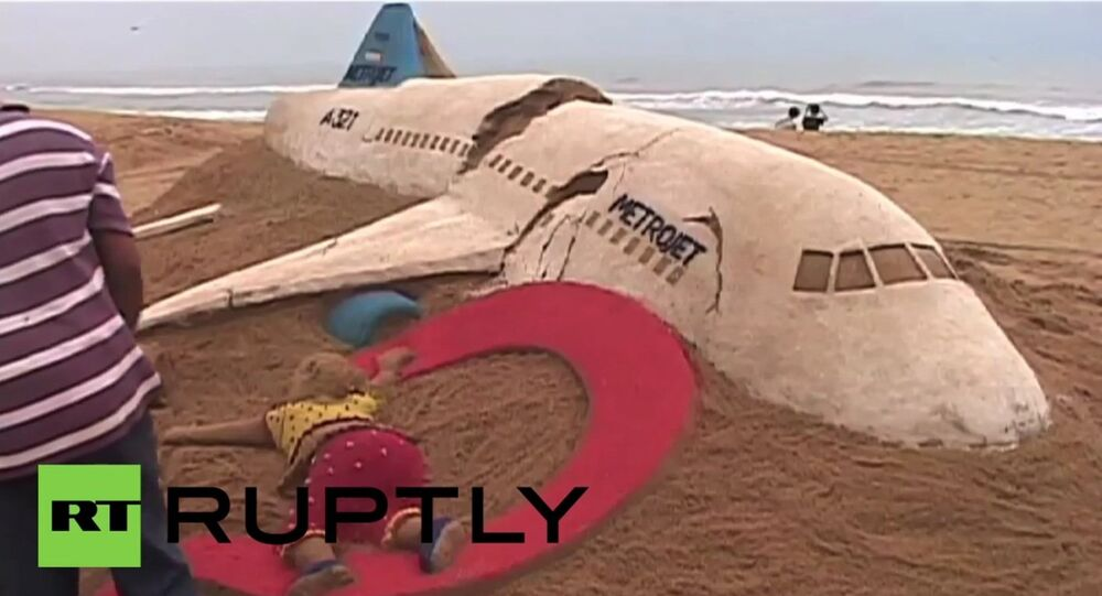 Indian artist Sudarsan Pattnaik creates 7K9268 plane sand sculpture in tribute to victims.