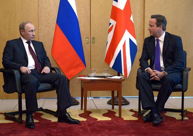 Russia's President Vladimir Putin (L) speaks with Britain's Prime Minister David Cameron (R).