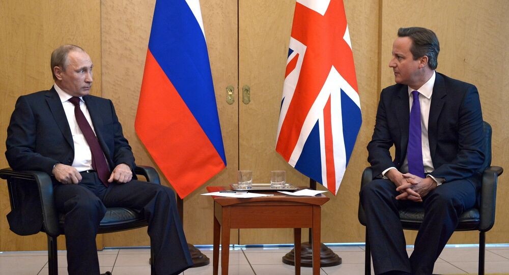 Russia's President Vladimir Putin (L) speaks with Britain's Prime Minister David Cameron (R).