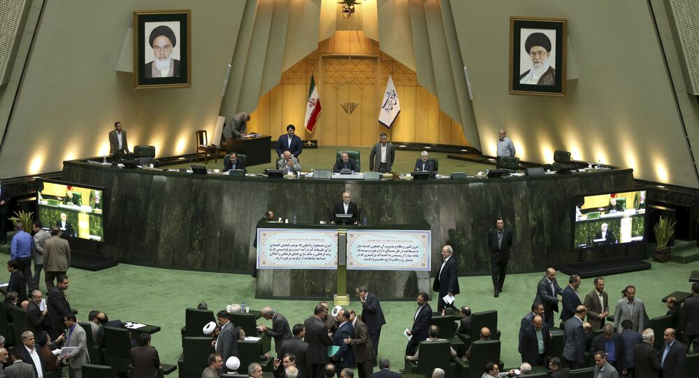 Head of Iran's Atomic Energy Organization Ali Akbar Salehi, center, speaks in an open session of parliament while discussing a bill on Iran's nuclear deal with world powers, in Tehran