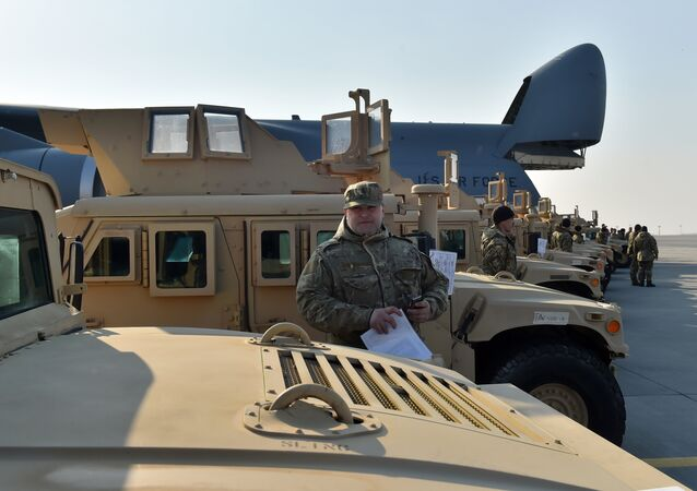 A Ukrainian serviceman holds a certificate at he stands next to an armoured car at Kiev airport on March 25, 2015 during a welcoming ceremony of the first US plane delivery of non-lethal aid, including 10 Humvee vehicles