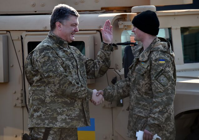 Ukrainian President Petro Poroshenko (L) shakes hands with an Ukrainian serviceman, the driver of one of the newly delivered an armoured vehicle, at Kiev airport on March 25, 2015 during a welcoming ceremony of the first US plane delivery of non-lethal aid, including 10 Humvee vehicles