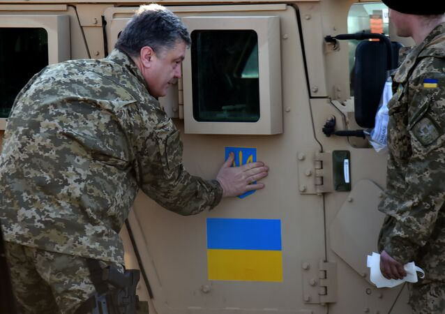Ukrainian President Petro Poroshenko sticks an Ukrainian flag and the state emblem on an armoured vehicle at Kiev airport on March 25, 2015 during a welcoming ceremony of the first US plane delivery of non-lethal aid, including 10 Humvee vehicles