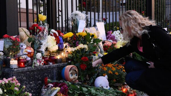 A woman lays flowers at the Russian Embassy in Kiev to mourn the victims of Kogalymavia's Airbus A321 passenger airliner - Sputnik International