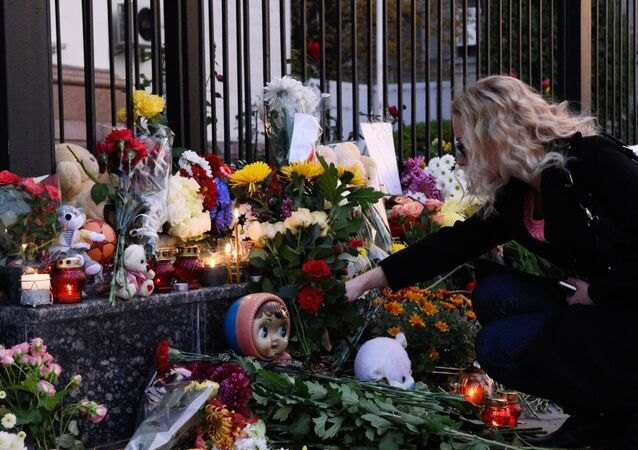 A woman lays flowers at the Russian Embassy in Kiev to mourn the victims of Kogalymavia's Airbus A321 passenger airliner