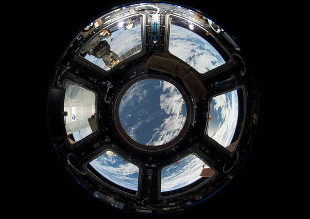 A view of Earth as seen from the Cupola on the Earth-facing side of the International Space Station. Visible in the top left foreground is a Russian Soyuz crew capsule. In the lower right corner, a solar array panel can be seen.