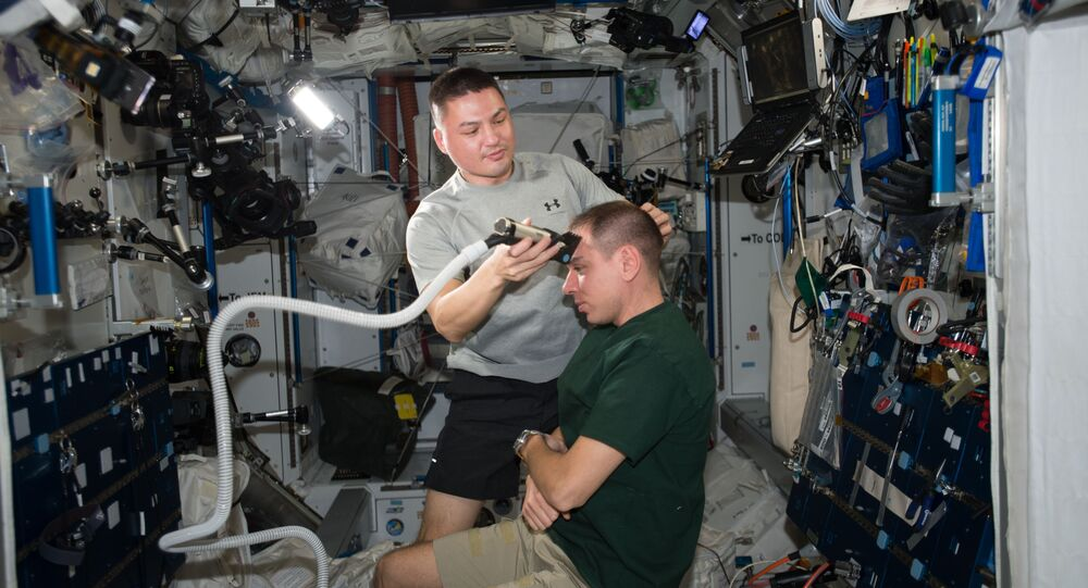 NASA astronaut Kjell Lindgren of Expedition 45 (left) provides a haircut to Russian cosmonaut Sergey Volkov (right) aboard the International Space Station. Not having a convienent barbershop 250 miles above the Earth, the crew helps each other out with a trimming of the locks from time to time.
