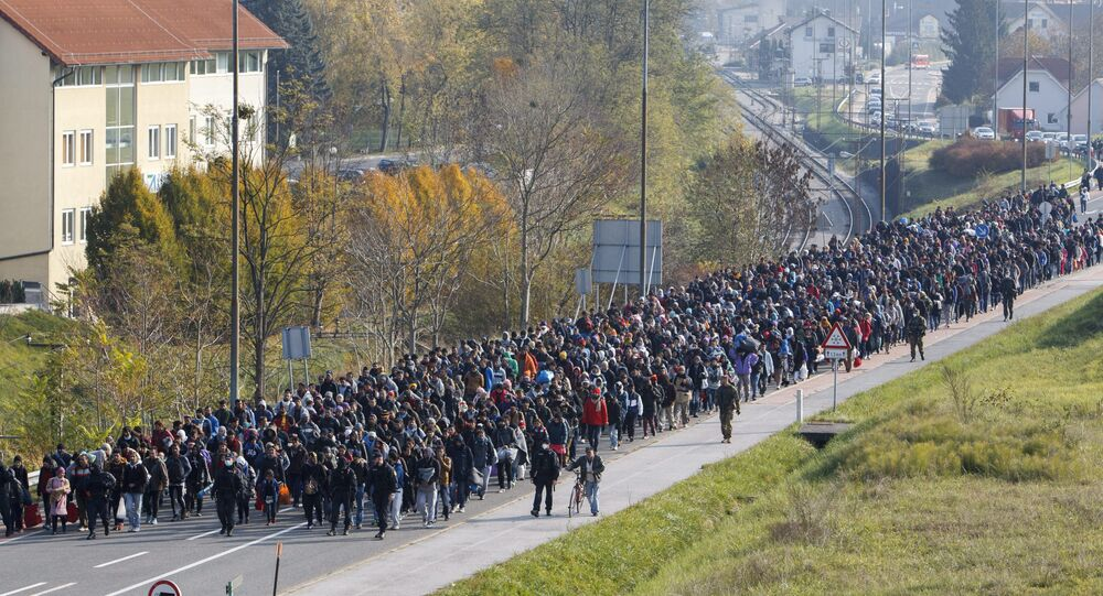 Migrants and refugee are escorted by Slovenian police officers toward the Slovenian-Austrian border crossing in Sentilj, Slovenia, Saturday, Oct. 31, 2015.
