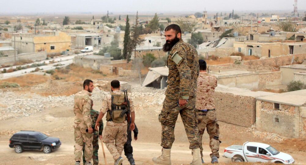 Syrian government forces walk in the village of Jabboul on the eastern outskirts of the northern Syrian city of Aleppo after taking control of the village from Islamic State (IS) group islamists