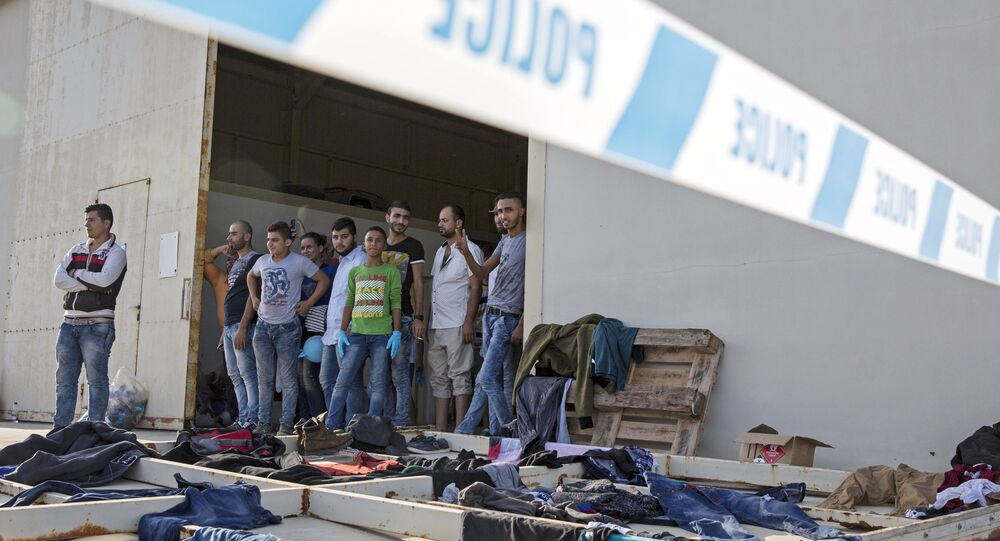 Syrian migrants are temporarily housed at a warehouse after coming ashore at RAF base Akrotiri, Cyprus, Wednesday, Oct. 21, 2015.