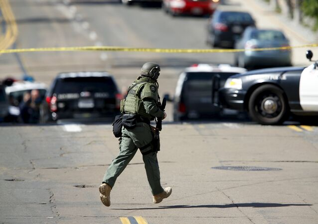 A SWAT team officer moves into position at the scene of an active shooting with a suspect with a high powered rifle in the Bankers Hills section of San Diego, California, November 4, 2015.