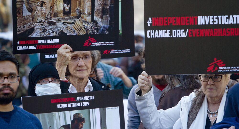 Supporters of Doctors Without Borders hold before and after images during a rally to mark the one-month anniversary of a U.S. military strike on its trauma center in Afghanistan.