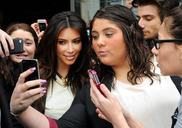 In this Friday, Sept. 21, 2012 file photo Kim Kardashian, left, is surrounded by her fans who are attempting to have their photographs taken with her as she leaves a radio station in Melbourne, Australia.