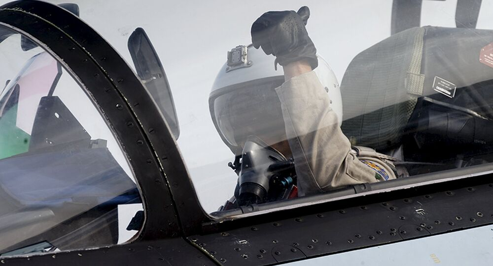 A pilot of a Sukhoi Su-30 fighter jet gestures before taking off at the Hmeymim air base near Latakia, Syria