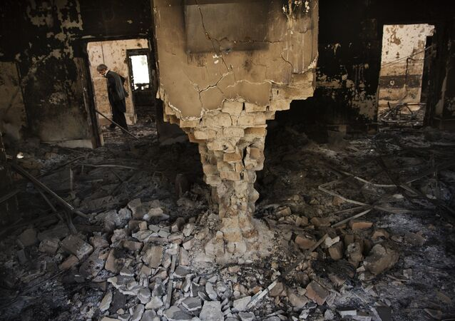 A man wearing a surgical mask walks, 14 October 2015, amongst the debris of the damaged and burnt-out MSF Trauma Centre in Kunduz, northern Afghanistan.