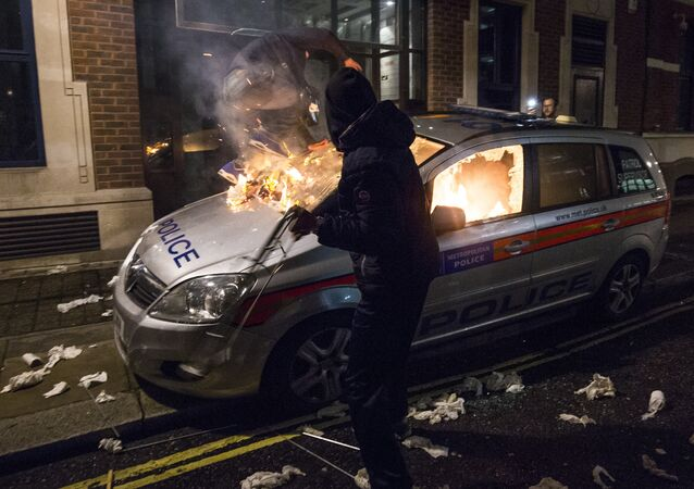 Anti-capitalist protesters attack a British police car during the Million Masks March, organised by the group Anonymous, near the Houses of Parliament in London on November 5, 2015.