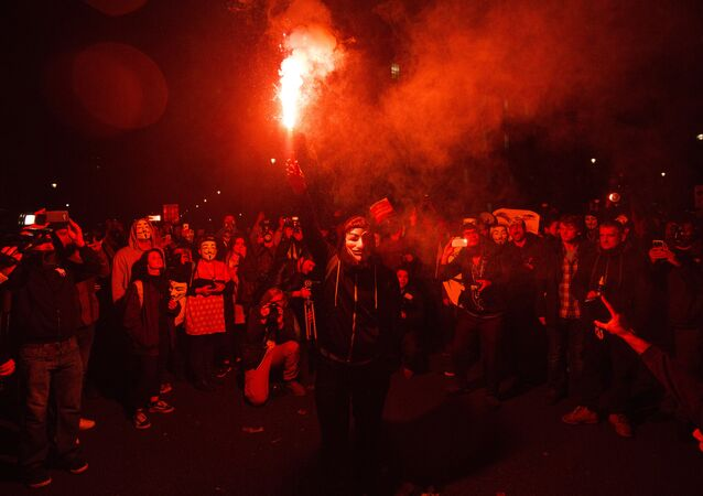 An anti-capitalist protester wearing a Guy Fawkes mask holds a lit flare during the Million Masks March, organised by the group Anonymous, near the Houses of Parliament in central London on 5 November 2015.