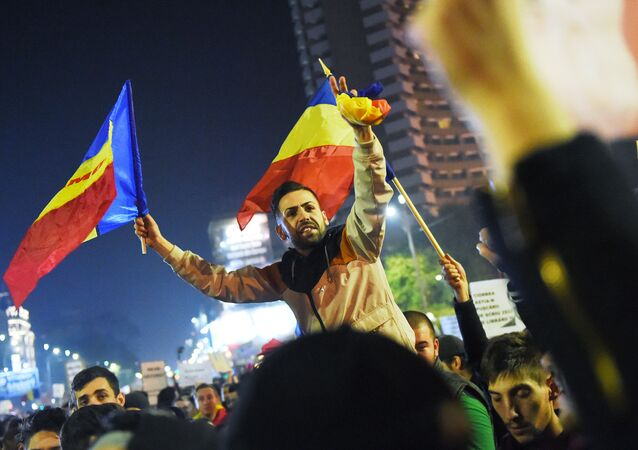 Protesters wave flags during a demonstration against the political class and Romanian authorities during the third day of protest in Bucharest on November 5, 2015.