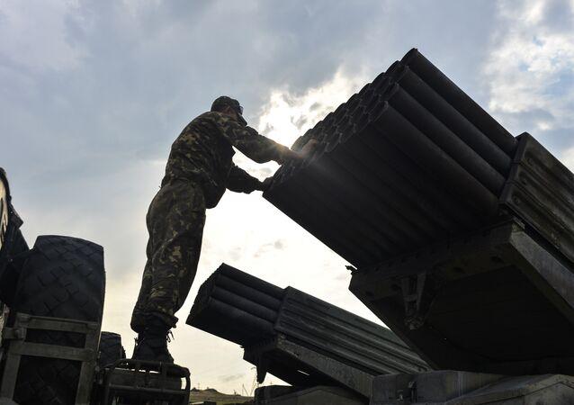 An Ukrainian soldier looks at a Grad multiple rocket launcher system, near the eastern Ukrainian city of Shchastya, Lugansk region, on August 18, 2014