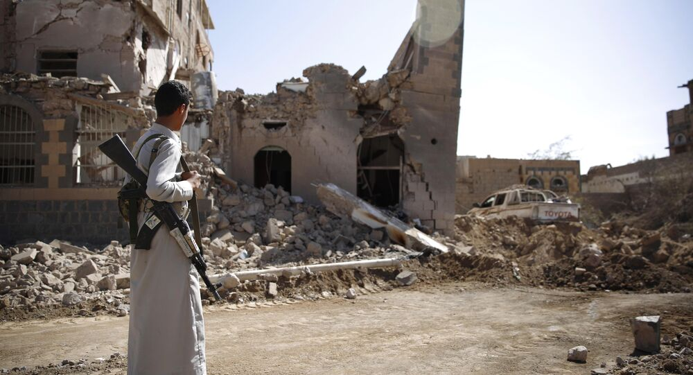 A Shiite fighter, known as a Houthi, look at a house destroyed by Saudi-led airstrikes in Sanaa, Yemen, Wednesday, Oct. 28, 2015