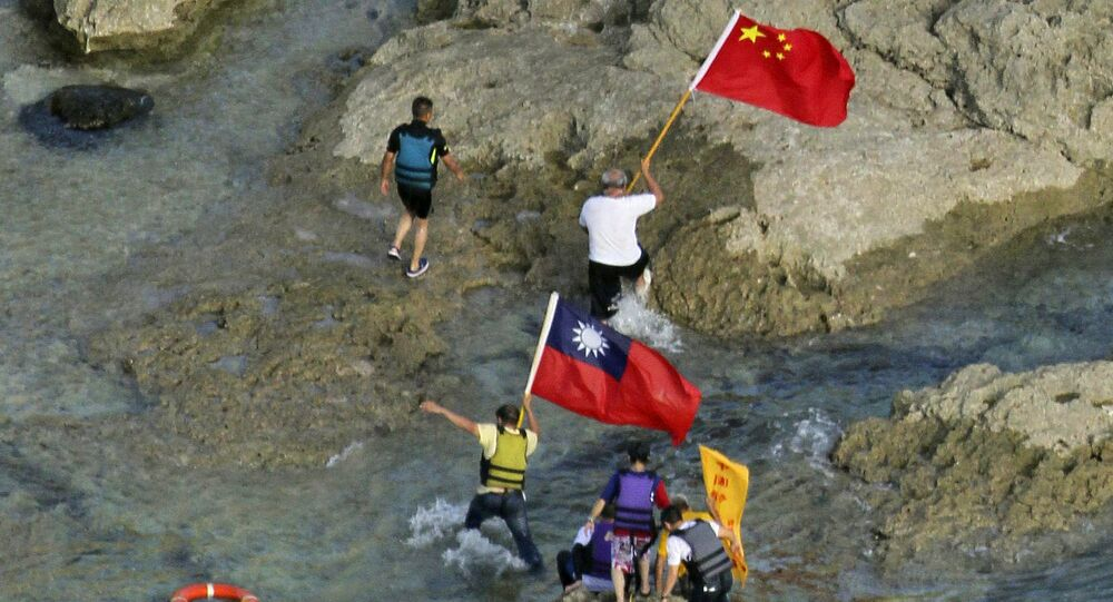 Activists in Taiwan carrying Chinese and Taiwanese national flags on the disputed island known as Senkaku in Japan and Diaoyu in China after arriving on their boat, west of Japan's sourthern island of Okinawa, August 12, 2012.
