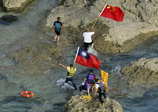 In a photograph taken on August 15, 2012, pro-China activists carrying Chinese and Taiwanese national flags walk on the disputed island known as Senkaku in Japan and Diaoyu in China after arriving on their boat, west of Japan's sourthern island of Okinawa