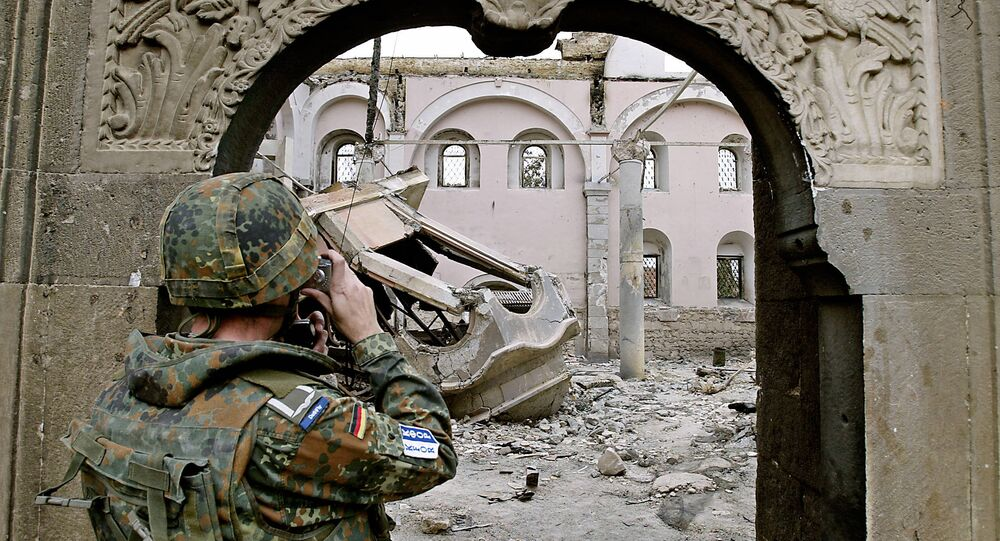 A German KFOR soldier takes photographs of the destroyed St. George Orthodox church in Prizren 22 March 2004