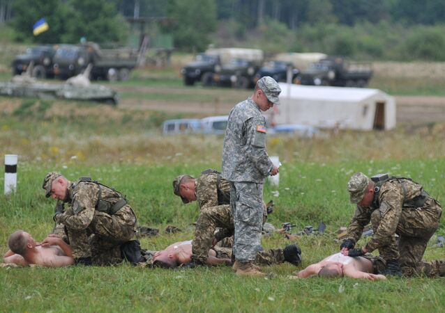 US serviceman teaches Ukrainian soldiers how to give emergency medical aid during the Rapid Trident/Saber Guardian 2015 military exercises at the International Peacekeeping and Security Centre base outside Lviv, Ukraine, Friday, July 24, 2015