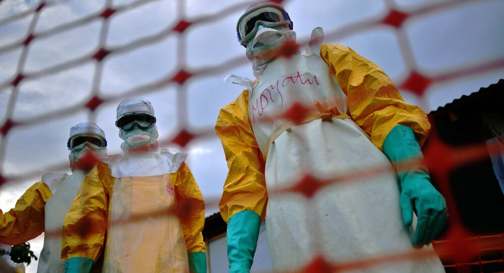 A file picture taken on August 14, 2014 shows Medecins Sans Frontieres (MSF) medical staff wearing protective clothing treating the body of an Ebola victim at their facility in Kailahun.