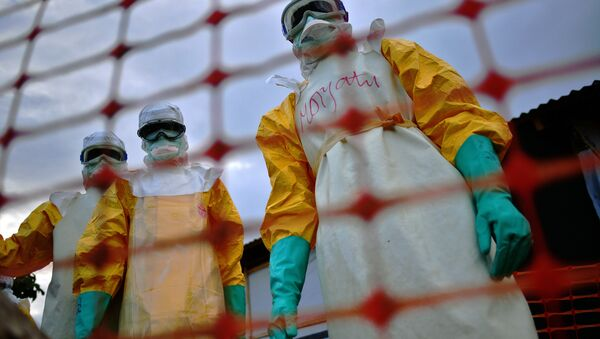 A file picture taken on August 14, 2014 shows Medecins Sans Frontieres (MSF) medical staff wearing protective clothing treating the body of an Ebola victim at their facility in Kailahun. - Sputnik International