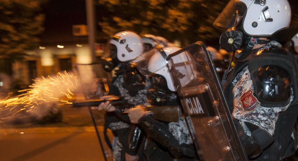 A riot policeman fires tear gas at protesters in front of the parliament building in Podgorica, Montenegro, October 24, 2015