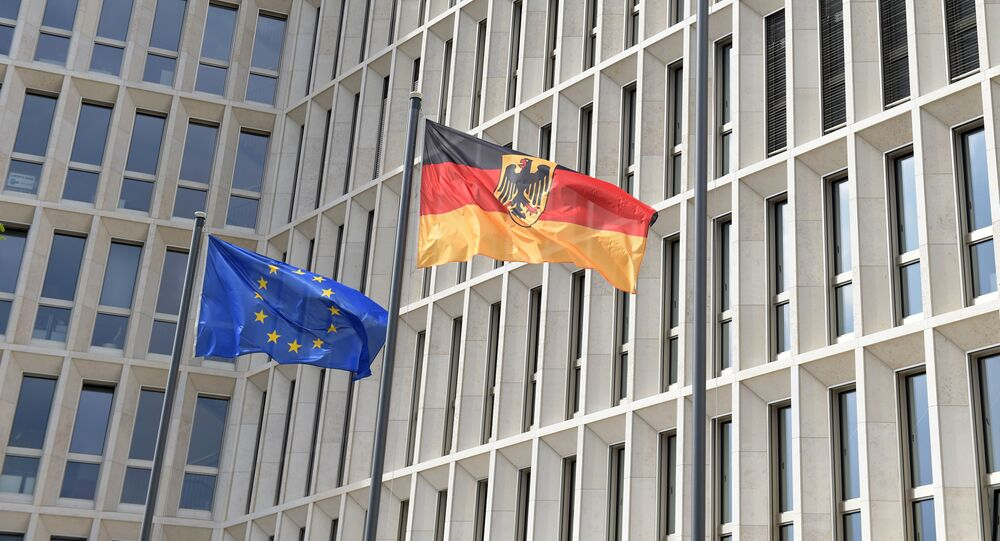 The German (R) and the European flag fly in the wind outside the new Federal Ministry of the Interior building.