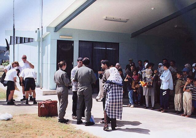 This file photo taken on August 19, 2001 shows officials (C-in green flight uniforms) questioning a refugee as other refugees (R), mostly believed to be from Iraq, wait in the shade before boarding an Australian Air Force Hercules aircraft on the Australian island territory of Christmas Island in the Indian Ocean.